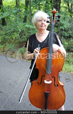 Female cellist. stock photo, Female cellist standing with his cello outside. by OSCAR Williams