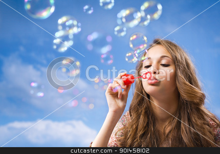 Bubble life. stock photo, Gorgeous young brunette girl blowing soap bubbles on blue sky. by exvivo