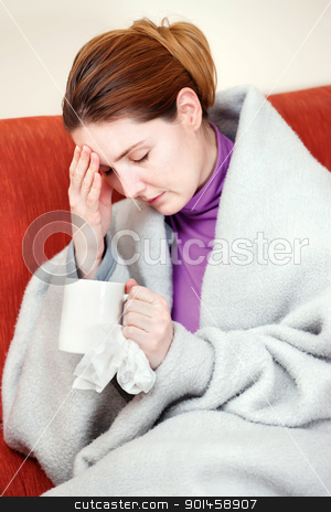 sick woman with a cup of tea in her hand stock photo, A young sick woman with a cup of tea in her hand. She hold her head in pain by iMarin
