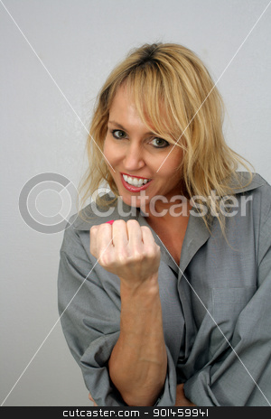 Beautiful Blonde Playfully Raises Her Fist stock photo, A lovely blonde with a captivating smile raises her fist to play-fight. by Carl Stewart