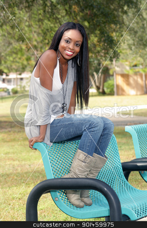 Beautiful Young Woman on a Park Bench (2) stock photo, An extraordinarily beautiful young woman with a bright, warm smile sits on a park bench. by Carl Stewart