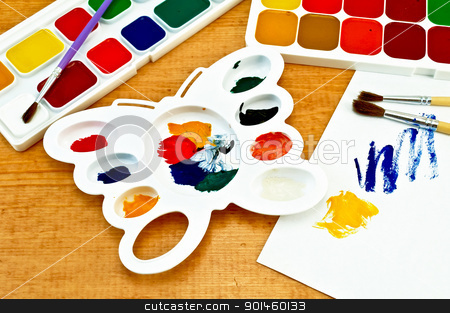 Paint palette and on the board stock photo, Two boxes of paint, three brushes, white palette in the shape of a butterfly, a piece of paper with a picture on a wooden board by rezkrr