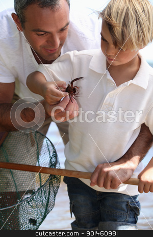Father and son with a crab on a beach stock photo, Father and son with a crab on a beach by photography33