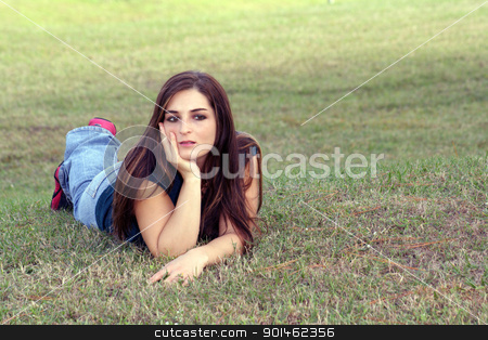 Lovely Young Brunette Outoors (6) stock photo, An attractive young brunette in casual wear relaxes outdoors, lying in the grass. by Carl Stewart