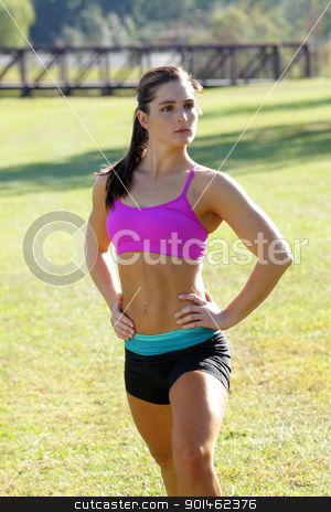 Beautiful Brunette Ahtlete Stretches Outdoors (1) stock photo, A lovely young brunette with remarkable abdominal musculature does stretching and warm-up outdoors. by Carl Stewart
