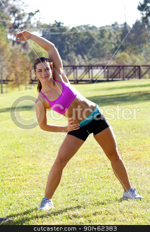 Beautiful Brunette Ahtlete Stretches Outdoors (4) stock photo, A lovely young brunette with remarkable abdominal musculature does stretching and warm-up outdoors. by Carl Stewart