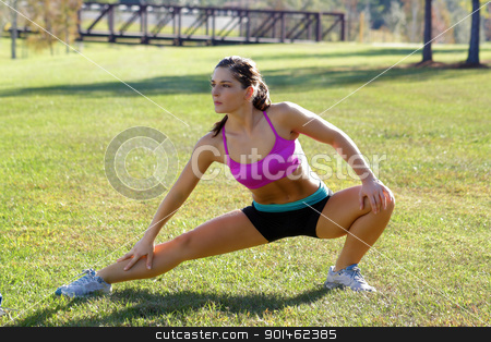 Beautiful Brunette Ahtlete Stretches Outdoors (6) stock photo, A lovely young brunette with remarkable abdominal musculature does stretching and warm-up outdoors. by Carl Stewart