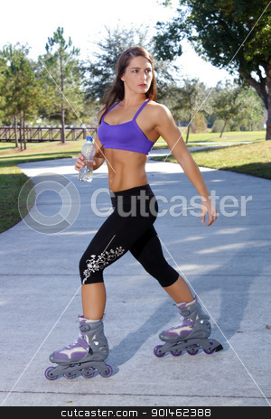 Beautiful Athletic Rollerblader Outdoors (1) stock photo, A lovely young brunette with remarkable abdominal musculature rollerblades outdoors. by Carl Stewart