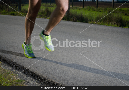 Running stock photo, Running sport shoes outdoors in action on country road. Male shoes on young man training. Slight motion blur, focus on back running shoe. by Homydesign
