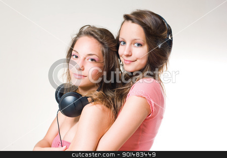 Our favourites. stock photo, A couple of gorgeous brunette teens listening to music in headphones. by exvivo