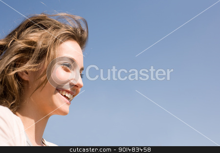 Young and free. stock photo, Gorgeous brunette woman smiling in the sunshine in front of blue sky. by exvivo