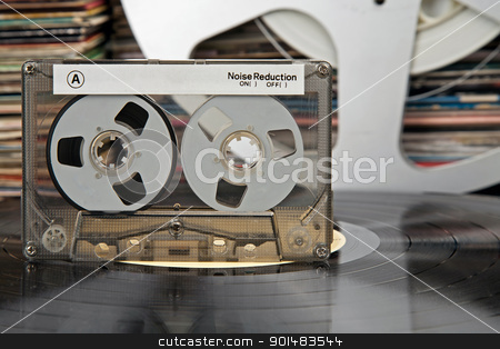 compact cassette and other stuff from that times stock photo, compact-cassette being on a vinyl record and audio analog tape and vinyl record covers in the distance by marekusz