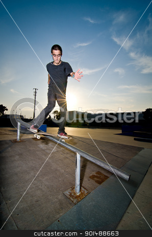 Skateboarder on a slide stock photo, Skateboarder on a slide at the local skatepark. by Homydesign
