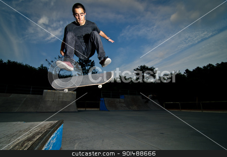 Skateboarder on a flip trick stock photo, Skateboarder on a flip trick at the local skatepark. by Homydesign