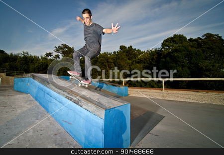 Skateboarder on a grind stock photo, Skateboarder on a grind at the local skatepark. by Homydesign