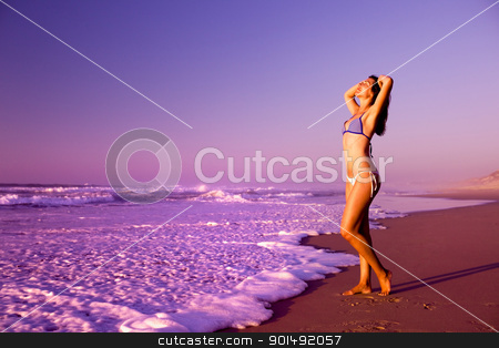 woman on the beach stock photo, Beautiful young woman relaxing at the sunset by ikostudio