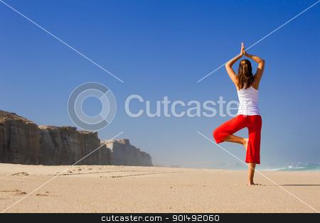 Young woman making Yoga stock photo, Beautiful young woman making Yoga exercises on the beach by ikostudio