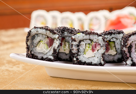 tuna sushi roll stock photo, sushi roll with tuna, avacado, sauce and flying fish roe, closeup by olinchuk