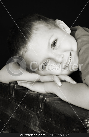 Beautiful boy stock photo, Beautiful blond boy lying on an antique trunk by Vanessa Van Rensburg