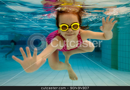 The girl smiles, swimming under water in the pool stock photo, The little girl in the water park swimming underwater and smiling by Antartis