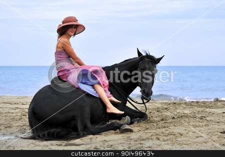 woman and  horse on the beach stock photo, beautiful black horse laid down on the beach and young woman by Bonzami Emmanuelle