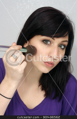 Beautiful Young Woman Applies Makeup (1) stock photo, A studio close-up of a lovely young woman with remarkable eyes, applying makeup with a brush. by Carl Stewart