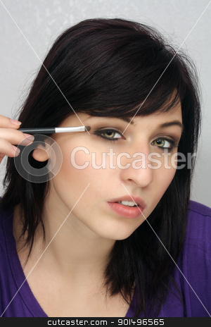 Beautiful Young Woman Applies Makeup (4) stock photo, A studio close-up of a lovely young woman with remarkable eyes, applying eye shadow with a small brush. by Carl Stewart