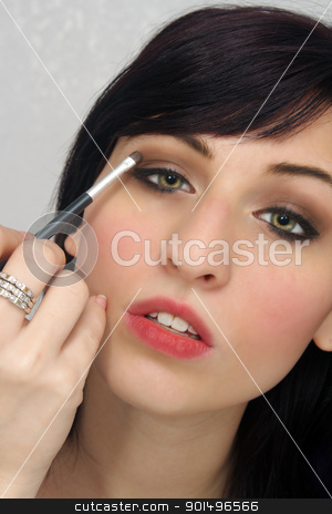 Beautiful Young Woman Applies Makeup (5) stock photo, A studio close-up of a lovely young woman with remarkable eyes, applying eye shadow with a small brush. by Carl Stewart