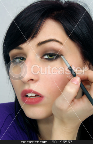 Beautiful Young Woman Applies Makeup (6) stock photo, A studio close-up of a lovely young woman with remarkable eyes, applying eye shadow with a small brush. by Carl Stewart