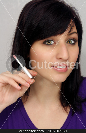 Beautiful Young Woman Holds a Cosmetics Applicator stock photo, A lovely young woman holds a lipstick or lip gloss applicator similar to the way a cigarette is commonly held. by Carl Stewart