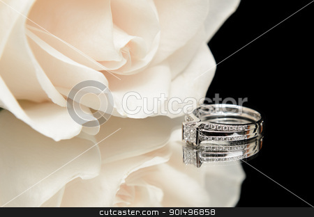 Diamond Engagement Ring stock photo, A diamond engagement ring with a white rose, shot with a reflection on a black background. by Richard Nelson