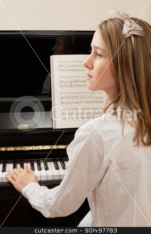 Piano practice stock photo, Photo of a young girl playing the piano at home. by © Ron Sumners
