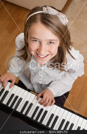 Playing the piano at home stock photo, Photo of a happy young girl playing the piano at home. by © Ron Sumners