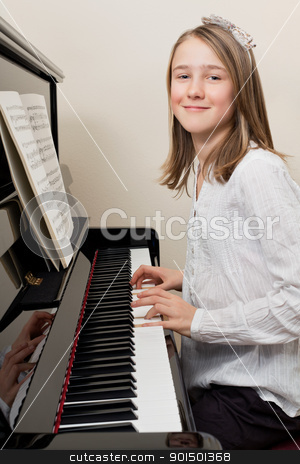 Happy young girl playing the piano stock photo, Photo of a young girl playing the piano at home. by © Ron Sumners