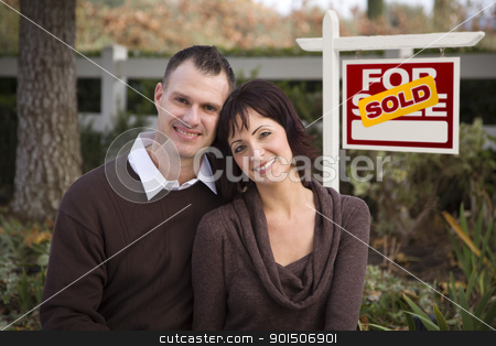 Happy Couple in Front of Sold Real Estate Sign stock photo, Happy Attractive Caucasian Couple in Front of Sold Real Estate Sign. by Andy Dean