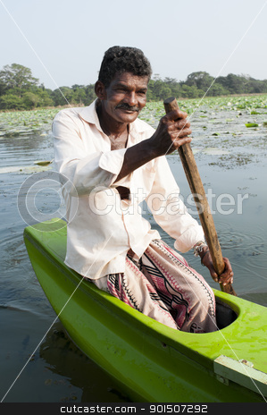 Smiling Asian man row a small traditional boat stock photo, Habarane, Sri Lanka - December 04, 2011: Smiling Sri Lankian man are floating by small traditional green boat upon a lake. by Iryna Rasko