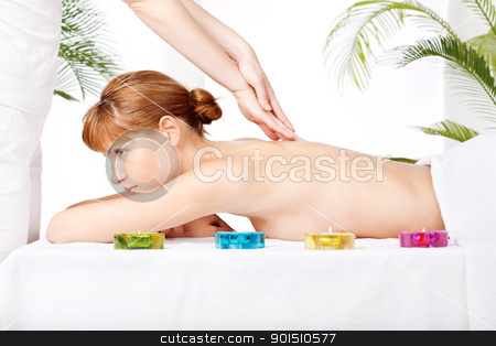 Back massage stock photo, Pretty woman getting a back massage in spa salon by iMarin