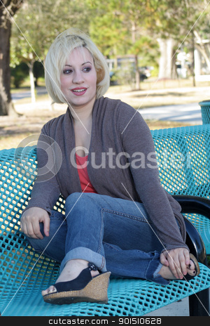 Beautiful Casual Blonde on a Park Bench (1) stock photo, A lovely young blonde in casual wardrobe, sitting on a park bench. by Carl Stewart