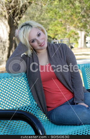 Beautiful Casual Blonde on a Park Bench (3) stock photo, A lovely young blonde in casual wardrobe, sitting on a park bench. by Carl Stewart