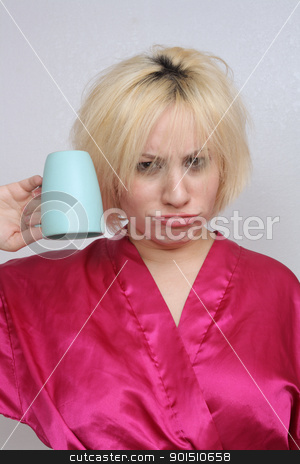 Grouchy Blonde with an Empty Coffee Cup stock photo, A disheveled frowning blonde wearing a bathrobe, holds an empty coffee cup upside down. by Carl Stewart