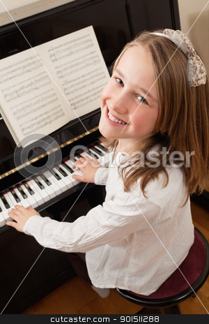 Smiling girl playing her piano stock photo, Photo of a young girl playing the piano at home. Sheet music has been altered to be unrecognizable. by © Ron Sumners