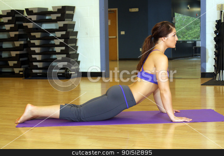 Beautiful Female Athlete at a Gym (2) stock photo, A lovely young, athletic brunette stretches on a mat at a gym. by Carl Stewart