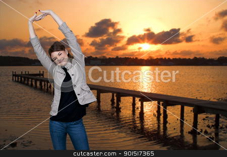 Woman at Sunrise stock photo, Beautiful woman stretching in a morning sunrise at the beach by Robert Byron