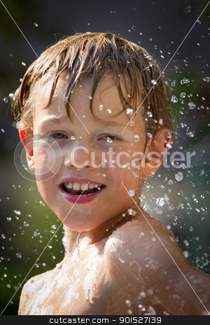 child playing in the water stock photo, Young child playing in the water by Christophe Rolland