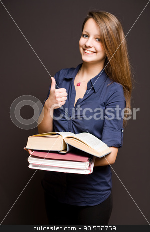 Cute student showing thumbs up. stock photo, Portrait of a cute young brunette student showing thumbs up. by exvivo