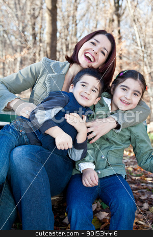 Laughing Mother Hugging Her Children stock photo, Family portrait of a happy laughing mother hugging smiling boy and girl. by Dasha Rosato