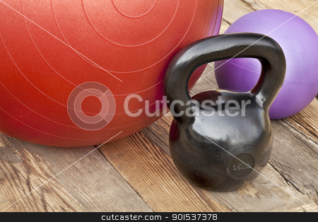 kettlebell and exercise balls stock photo, black iron kettlebell, Swiss and medicine exercise balls on wooden deck - fitness concept by Marek Uliasz