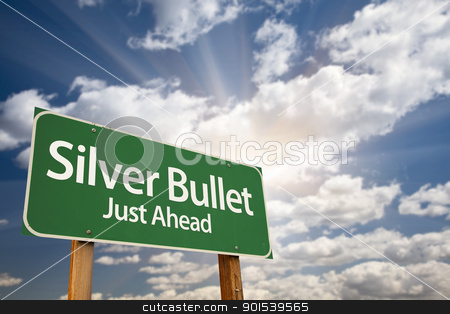 Silver Bullet Just Ahead Green Road Sign and Clouds stock photo, Silver Bullet Just Ahead Green Road Sign with Dramatic Clouds, Sun Rays and Sky. by Andy Dean