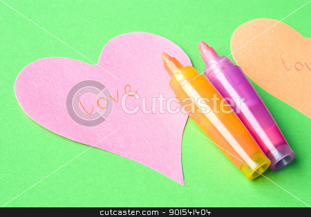 Love word stock photo, Word LOVE written on a pink heart arranged with colorful felt tip pens and green background. Love concept. by Tiramisu Studio