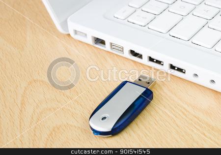 Laptop and flash pen drive stock photo, Laptop and flash pen drive arranged on wooden table by Tiramisu Studio